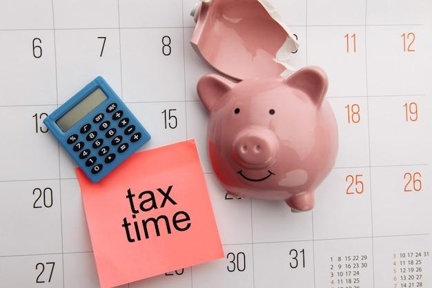 Cofrinho quebrado em um calendário branco. conceito de imposto e poupança