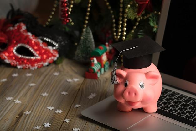Cofrinho rosa com chapéu de pós-graduação em um laptop.