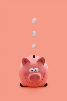 Cofrinho rosa com moedas caindo
