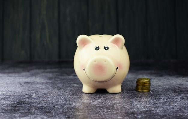 Cofrinho rosa com moedas para investimento e um banco em um fundo de madeira para poupança