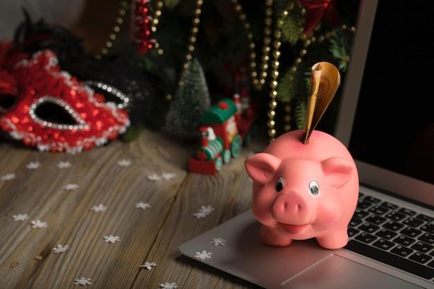 Cofrinho rosa com notas em um laptop close