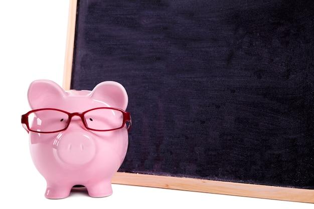Cofrinho rosa com óculos ao lado de um quadro-negro