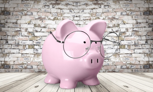 Cofrinho rosa com óculos no fundo da parede de tijolos, conceito de economia de dinheiro inteligente