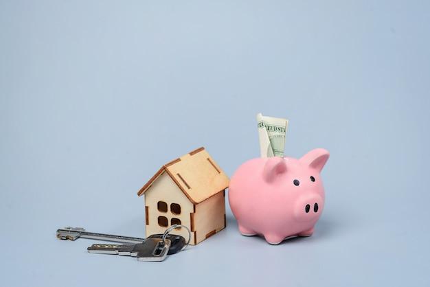 Cofrinho rosa e casa de brinquedo de madeira sobre uma superfície cinza