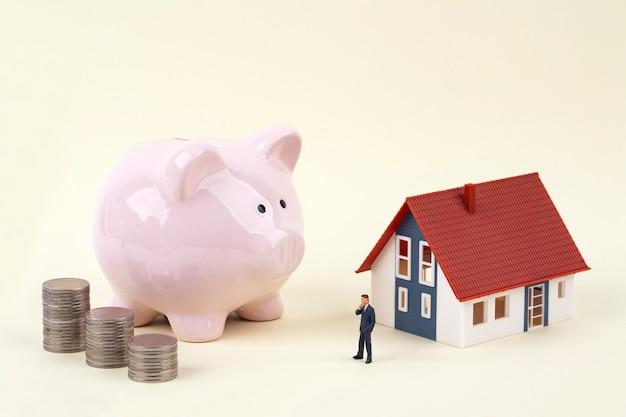 Cofrinho rosa e empresário em miniatura com casa modelo