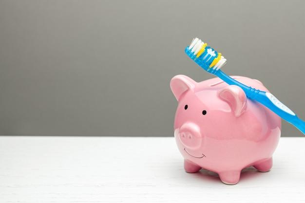 Cofrinho rosa e escova de dentes em fundo cinza o conceito de como economizar no tratamento dentário