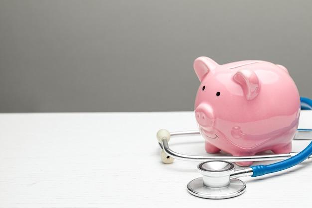 Cofrinho rosa e estetoscópio sobre um fundo cinza conceito de como economizar no seguro de saúde