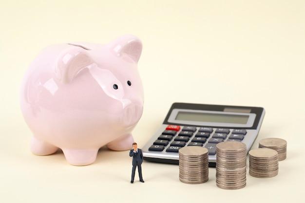 Cofrinho rosa e moedas com empresário em miniatura