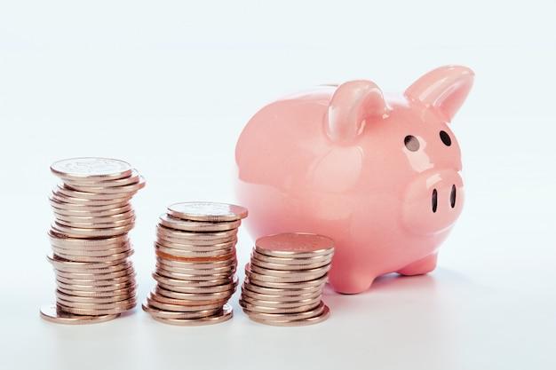 Cofrinho rosa e moedas isoladas no branco