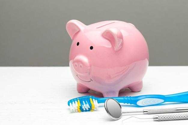 Cofrinho rosa e utensílios odontológicos com uma escova de dentes em um fundo cinza o conceito de como economizar