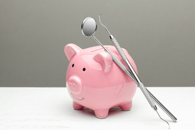 Cofrinho rosa e utensílios odontológicos em fundo cinza. o conceito de como economizar no tratamento odontológico.