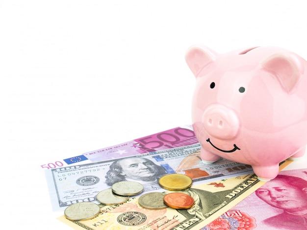 Cofrinho rosa em dólares, chinês, notas de euro, isolado no fundo branco, conceito de poupança