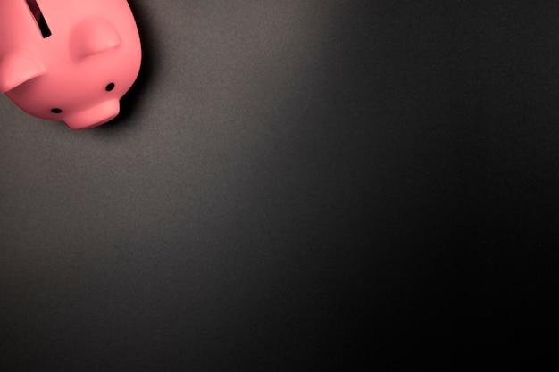 Cofrinho rosa em uma vista superior de fundo preto com cópia de espaço, economia financeira e conceito de negócios