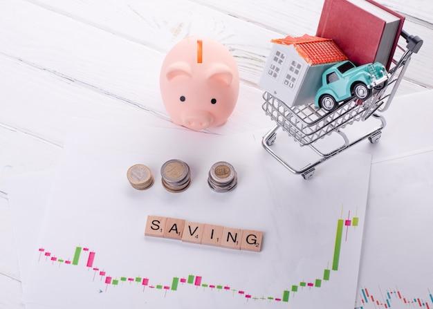 Cofrinho rosa, moedas e casa, carro e livro no carrinho em gráficos de crescimento de investimento