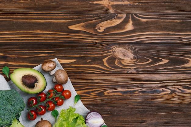 Cogumelo; abacate; tomate cereja; cebola; brócolis na toalha de mesa contra a mesa de madeira