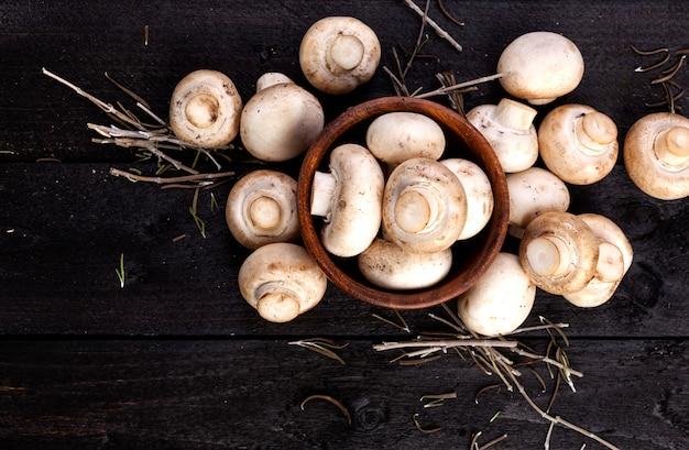 Cogumelo branco fresco dos cogumelos em preto de madeira. vista do topo. copie o espaço.
