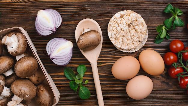 Cogumelo; cebola cortada ao meio; tomate cereja; ovos e bolo de arroz tufado contra a mesa de madeira