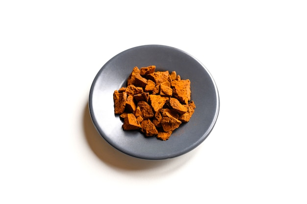 Cogumelo chaga. pequenos pedaços picados secos de chaga de fungo de árvore de vidoeiro em um prato redondo isolado em uma parede branca. conceito de medicina natural alternativa