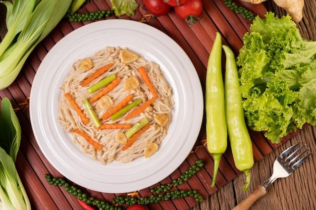 Cogumelo com agulha dourada frito em um prato branco com alho