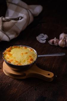 Cogumelo cozido com frango e queijo em uns potenciômetros do metal em de madeira.