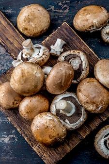 Cogumelo de portobello na placa de madeira. vista superior escura
