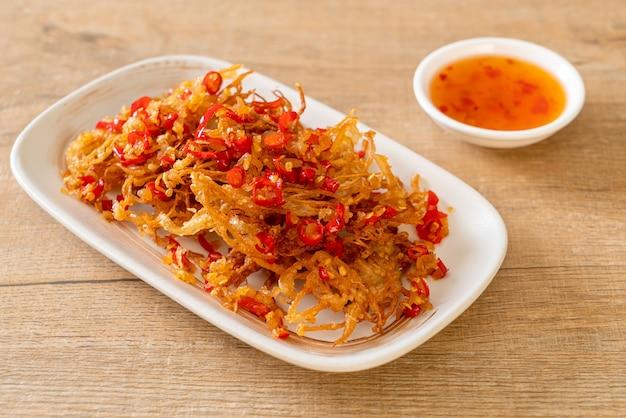 Cogumelo enoki frito ou cogumelo agulha dourada com sal e pimenta - estilo de comida vegana e vegetariana