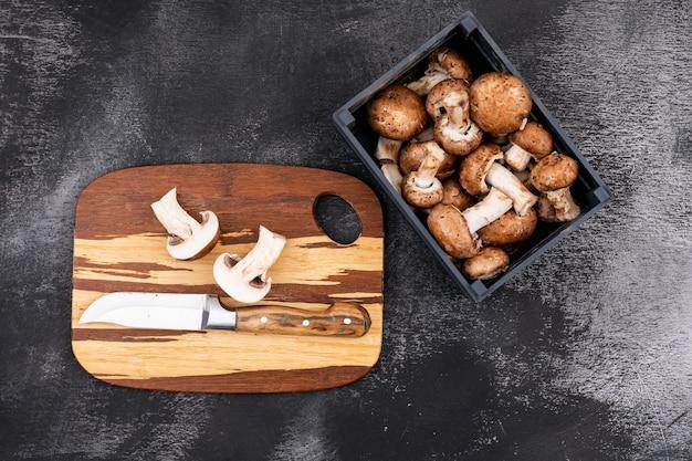 Cogumelo fatiado com uma faca na tábua de madeira perto de caixa de madeira com cogumelos frescos