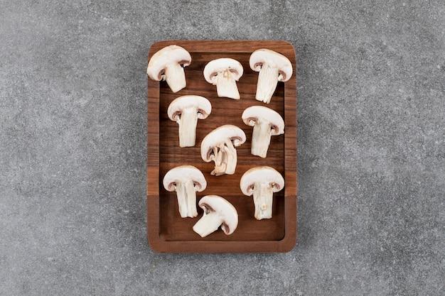 Cogumelo fatiado em uma placa de madeira sobre uma superfície cinza