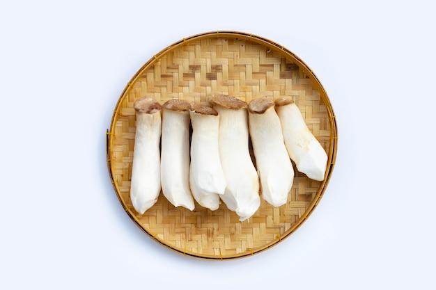 Cogumelo king oyster em uma cesta de bambu em uma superfície branca
