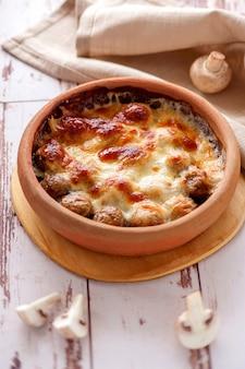 Cogumelos assados com queijo em louça de barro. prato vegetariano quente. vertical.
