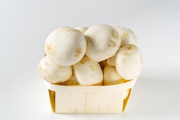 Cogumelos brancos cogumelos na cesta de madeira em um fundo claro. feche com espaço de cópia. champignon embalado na cesta.
