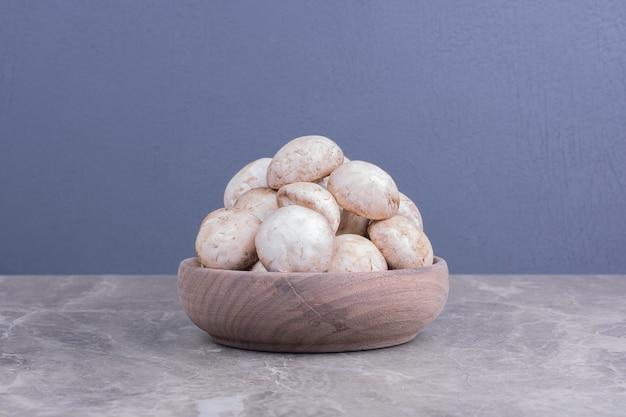 Cogumelos brancos em um copo de madeira na superfície cinza