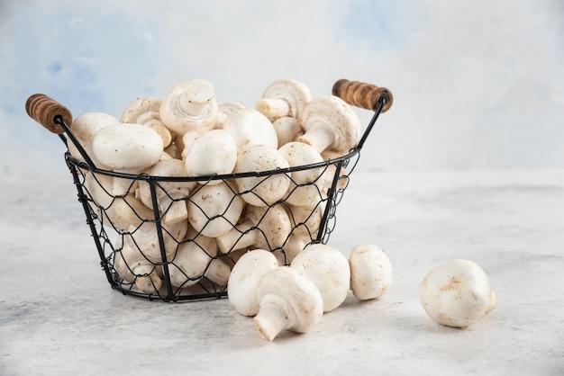 Cogumelos brancos em uma bandeja metálica na mesa de mármore.