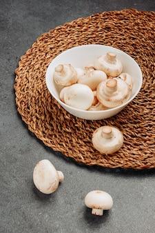 Cogumelos brancos em uma tigela sobre um trivet de vime e cinza de plano de fundo texturizado. vista de alto ângulo.