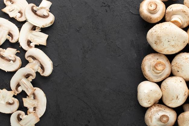 Cogumelos brancos frescos champignon fatiado e maduro em fundo escuro
