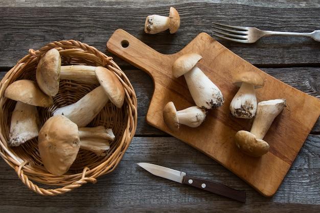 Cogumelos brancos frescos na cesta para cozinhar na placa de madeira.