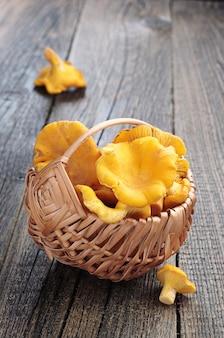 Cogumelos cantarelos em uma pequena cesta com fundo de madeira