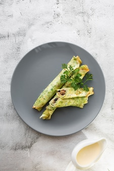 Cogumelos caseiros salgados e espinafres crepes verdes com queijo isolado no fundo de mármore branco. comida caseira. saboroso café da manhã. foco seletivo. foto vertical.