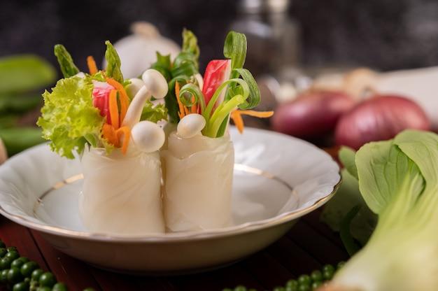 Cogumelos, cenouras, aspargos e alface amarrados com macarrão