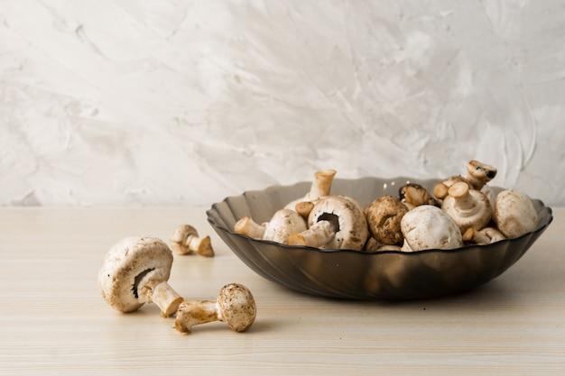 Cogumelos champignon em chapa de madeira whte brilhante