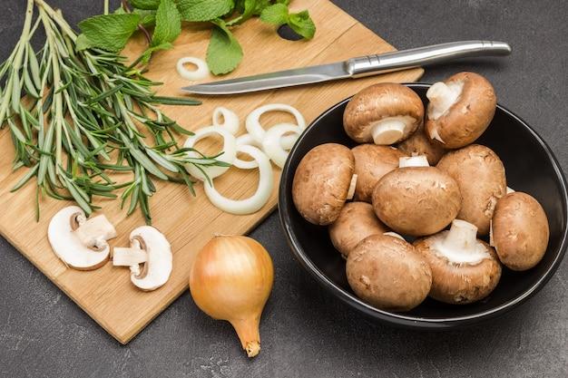 Cogumelos champignon em uma tigela preta, cebolas picadas e cogumelos na tábua de cortar com raminhos de hortelã e alecrim