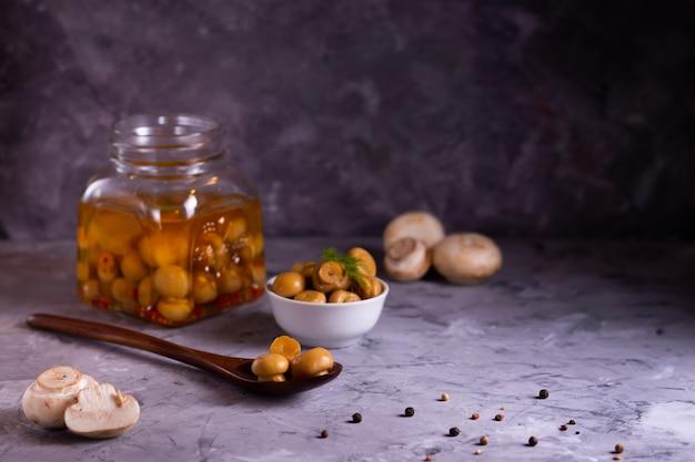 Cogumelos champignon fermentados em lata em uma colher de madeira ecológica e em uma jarra de vidro com alho, folha de louro em tom baixo