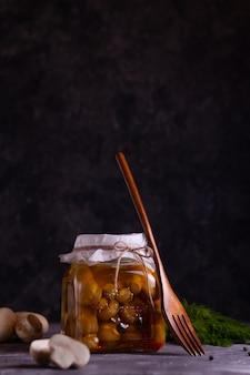 Cogumelos champignon fermentados em lata em uma jarra de vidro com alho, louro e endro com um garfo de madeira em uma chave baixa