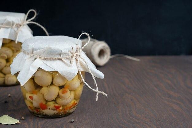 Cogumelos champignon marinados ou fermentados em lata ou frasco de vidro na mesa de madeira escura