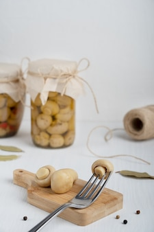Cogumelos champignon marinados servidos em uma tábua com mesa de madeira branca em forma de garfo na cozinha