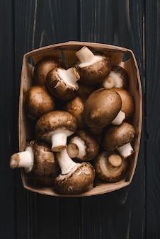 Cogumelos champignon real cru fresco na caixa de papelão na mesa de madeira preta