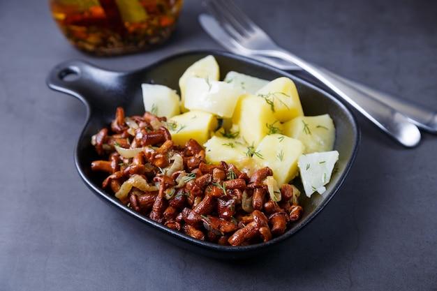 Cogumelos chanterelle com batata cozida, cebola, endro e azeite em uma pequena panela preta. prato tradicional russo
