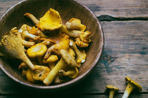 Cogumelos chanterelle em um fundo de madeira. cogumelos crus em uma tigela de madeira.