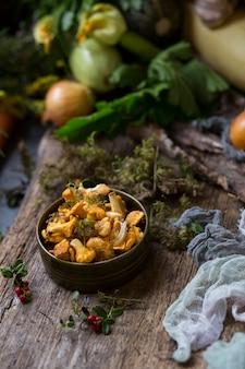 Cogumelos chanterelle em um prato de barro e legumes na vista superior de fundo