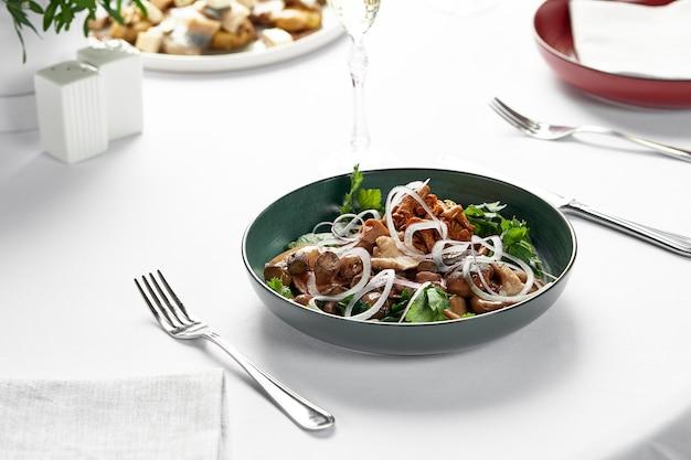 Cogumelos com cebola e ervas, cogumelos em conserva variados num prato sobre fundo claro, cogumelos marinados com ervas frescas e cebolas.